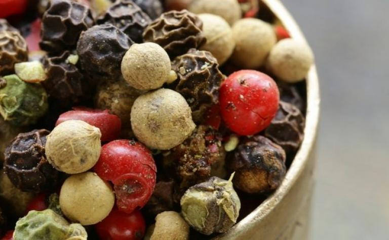 Zwarte, witte, groene en rode peper